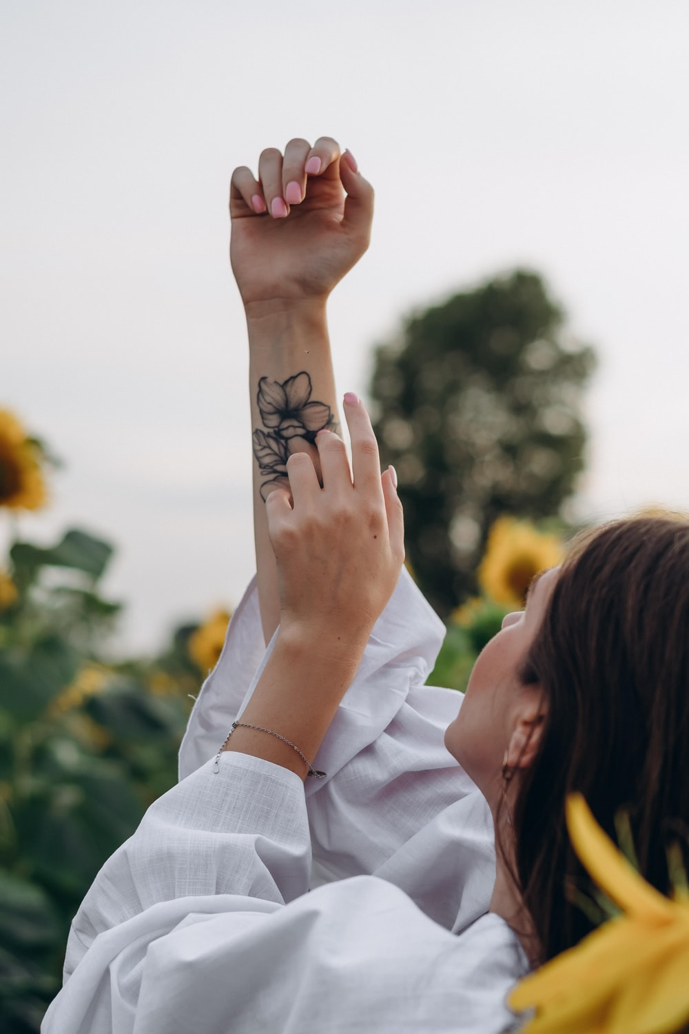 woman with black and white floral tattoo on left hand