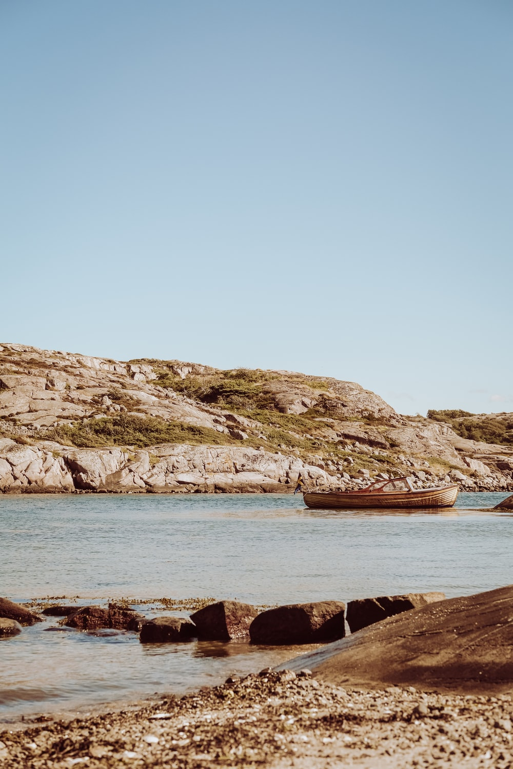 brown boat on sea near brown rock formation during daytime