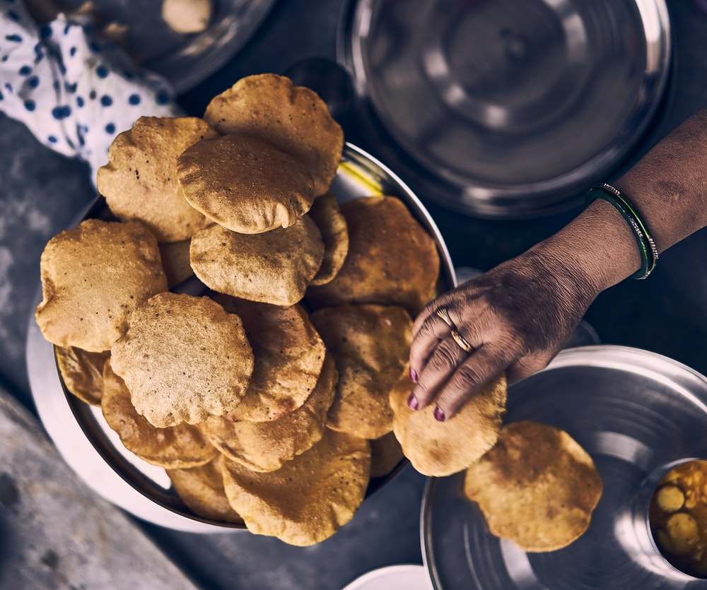 person holding brown cookies on blue and white ceramic plate