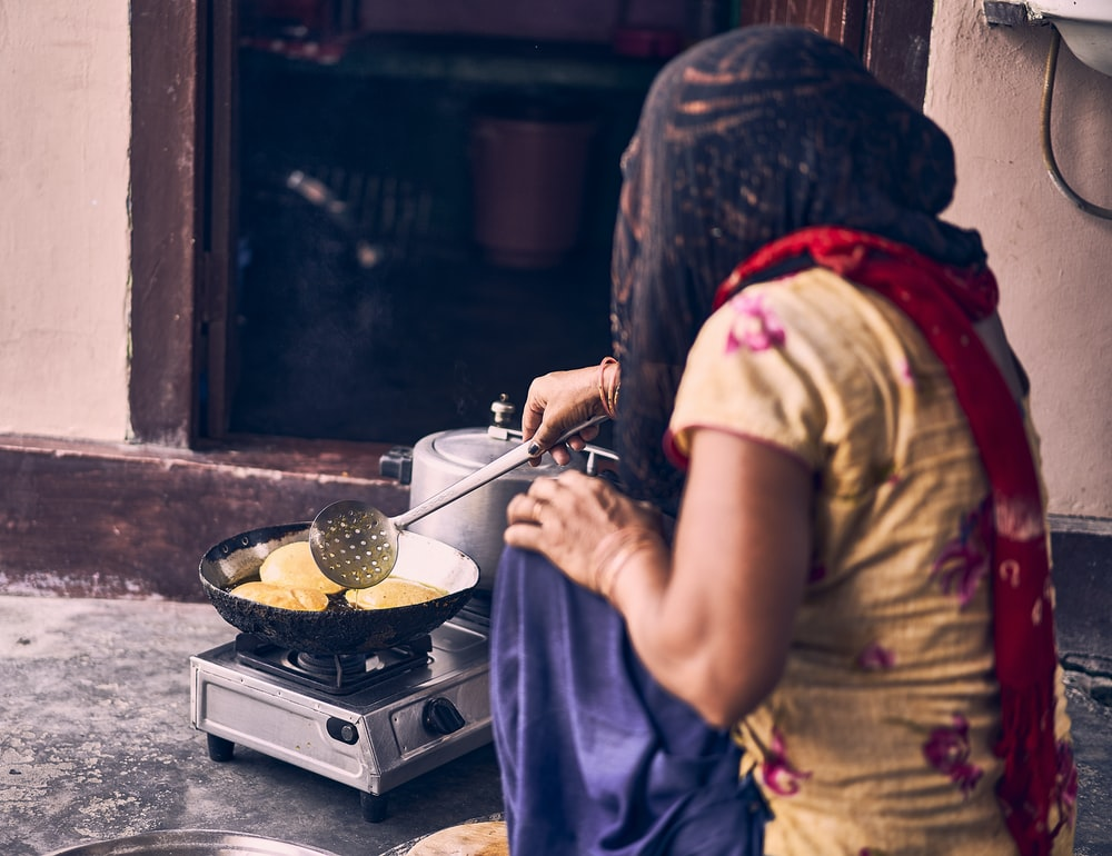 woman in brown shirt holding stainless steel cooking pot