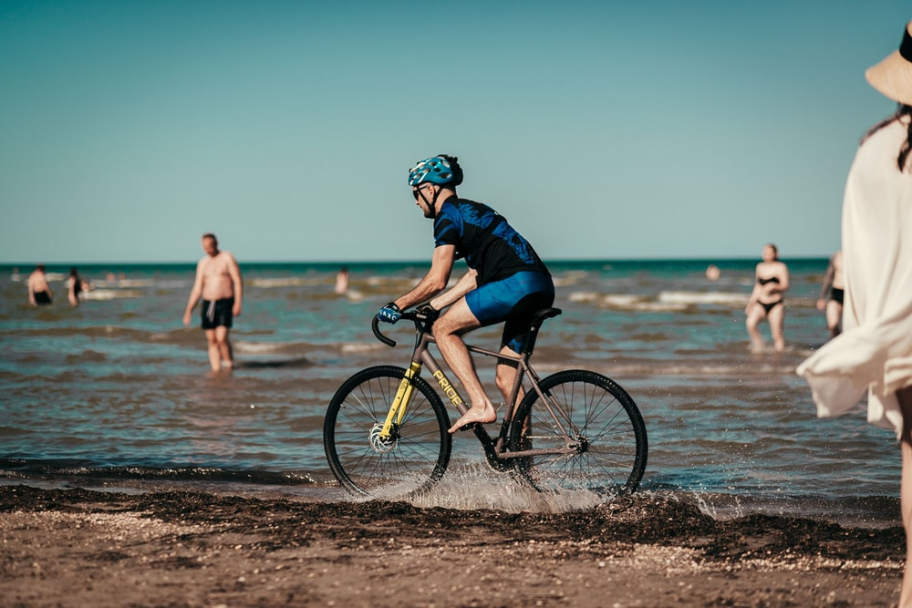 man in black jacket riding on bicycle on beach during daytime