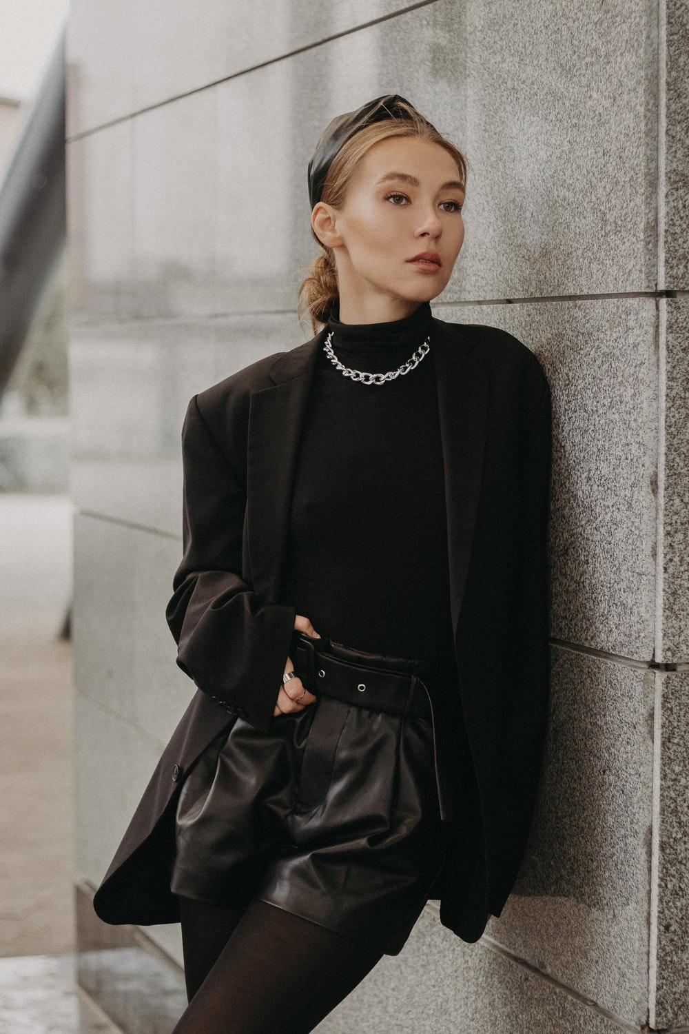woman in black long sleeve dress leaning on gray concrete wall during daytime