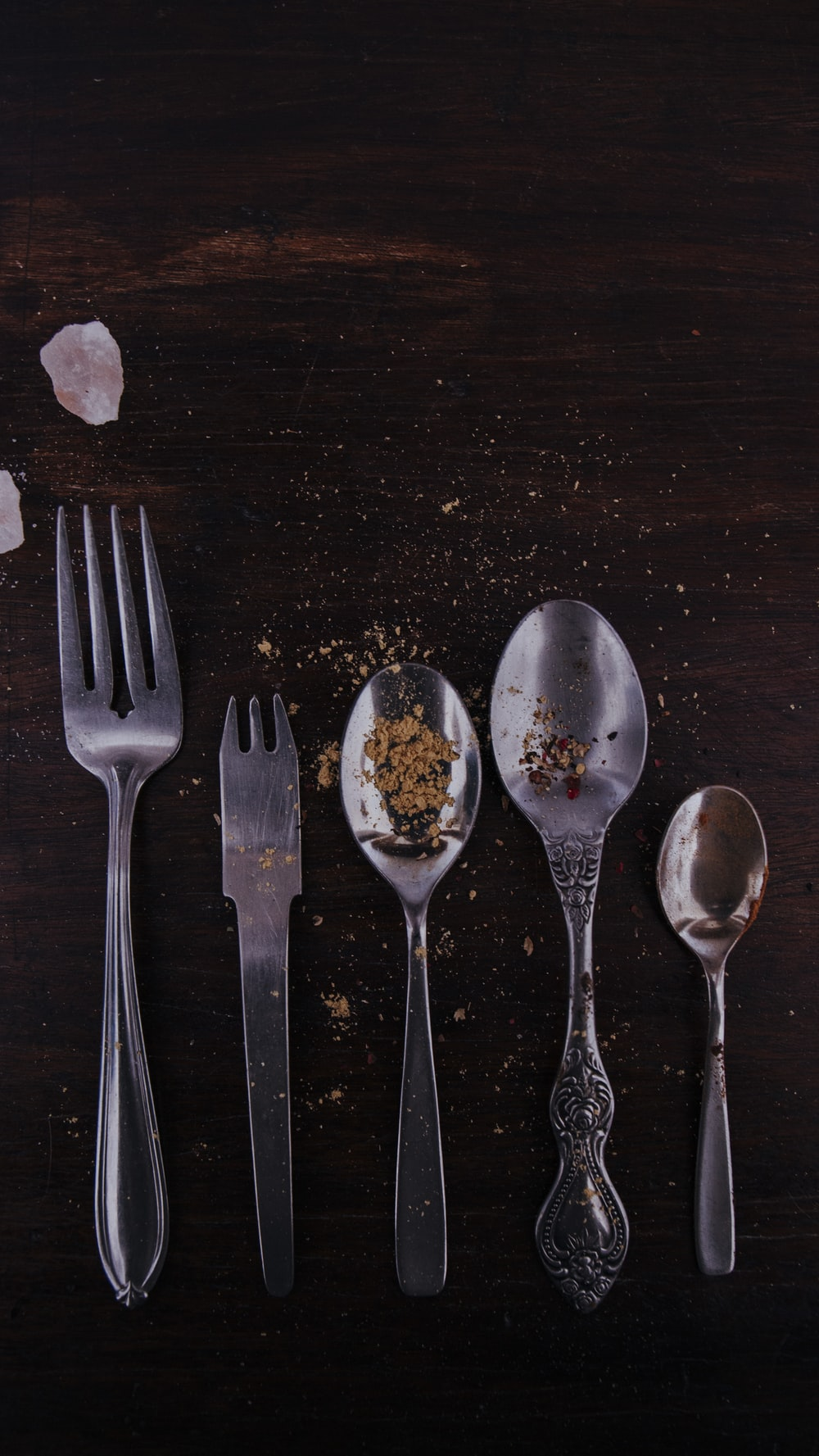 stainless steel spoons and fork on brown wooden table