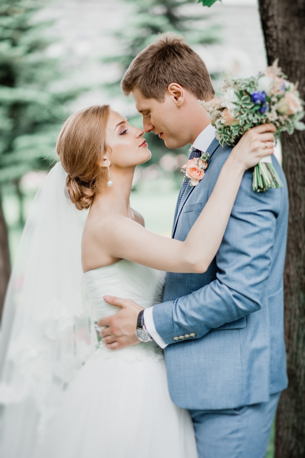 man in gray suit kissing woman in white dress