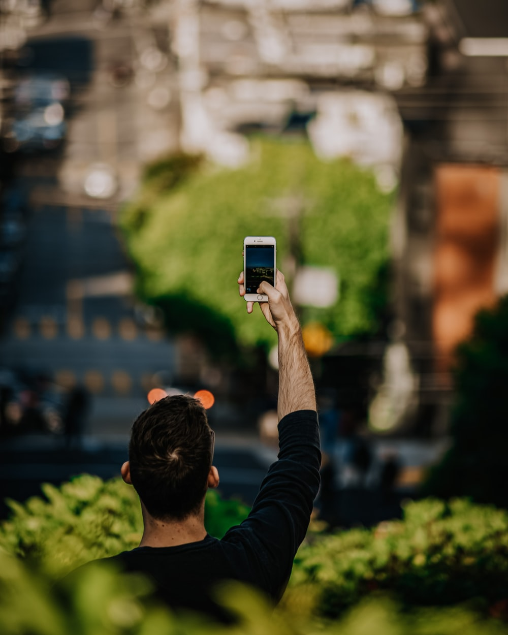 man in black long sleeve shirt holding black smartphone taking photo of city buildings during daytime