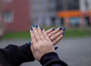 person with blue manicure and blue manicure