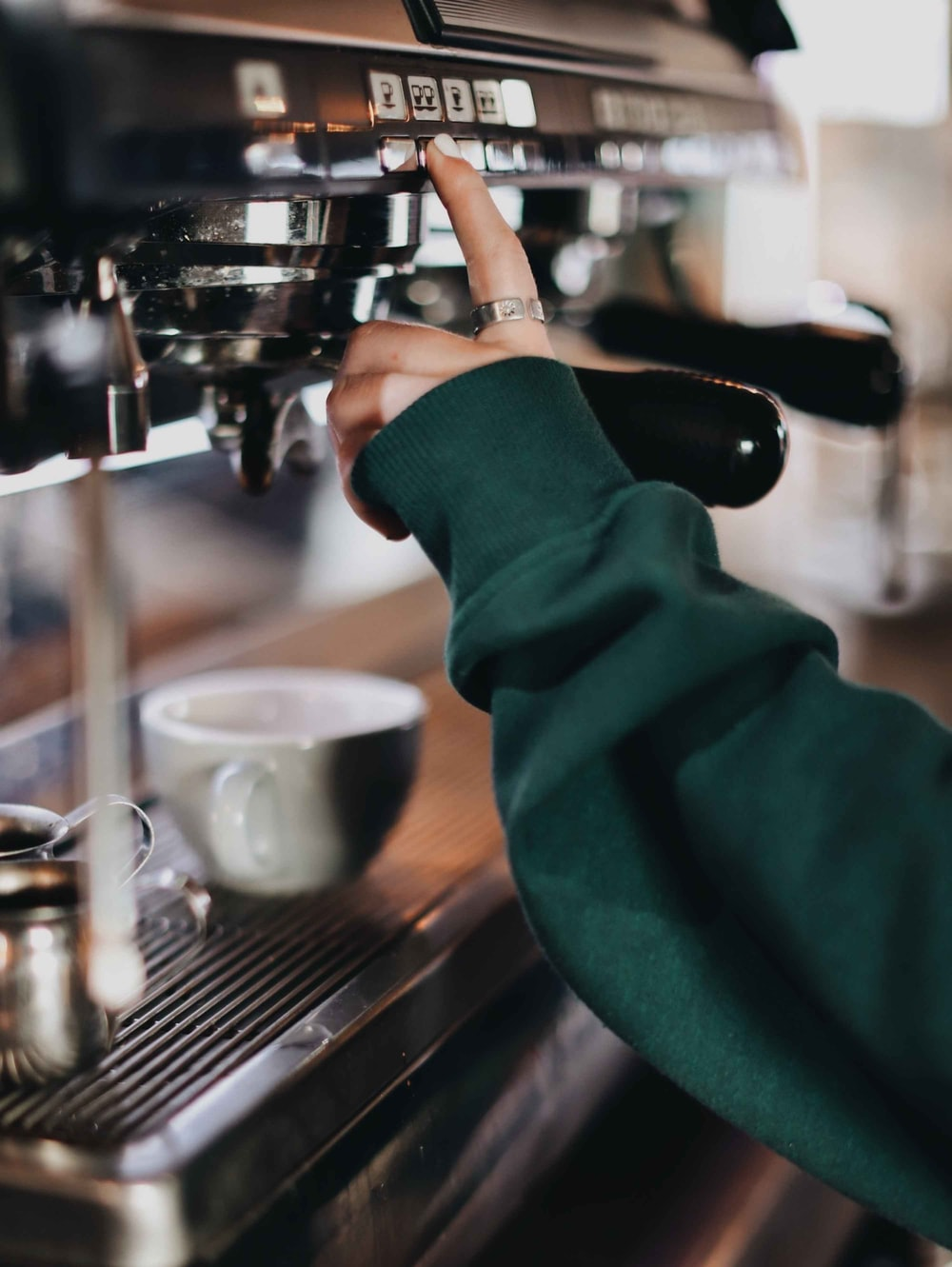 person in green long sleeve shirt holding silver and black espresso machine