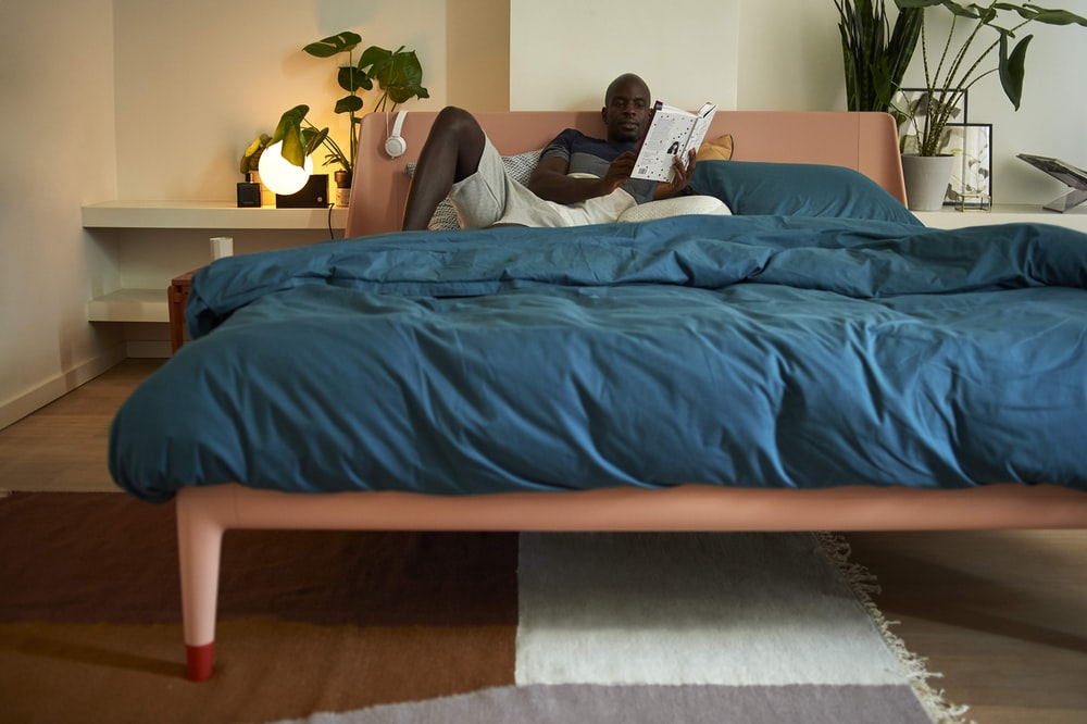 man in black t-shirt and gray pants lying on blue bed