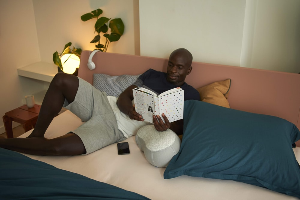 man in gray t-shirt lying on bed reading book