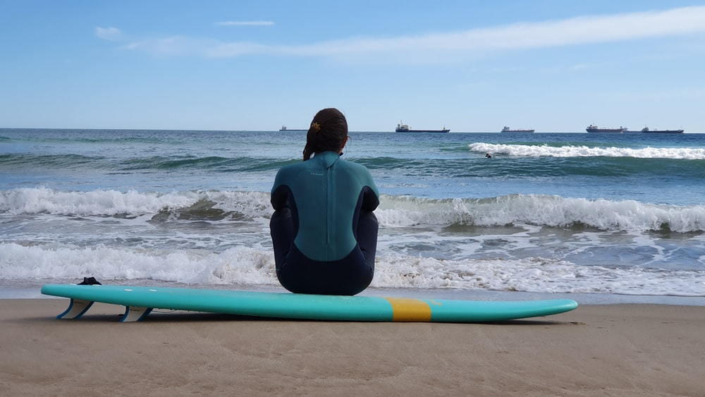 man in black wet suit sitting on blue surfboard on beach during daytime