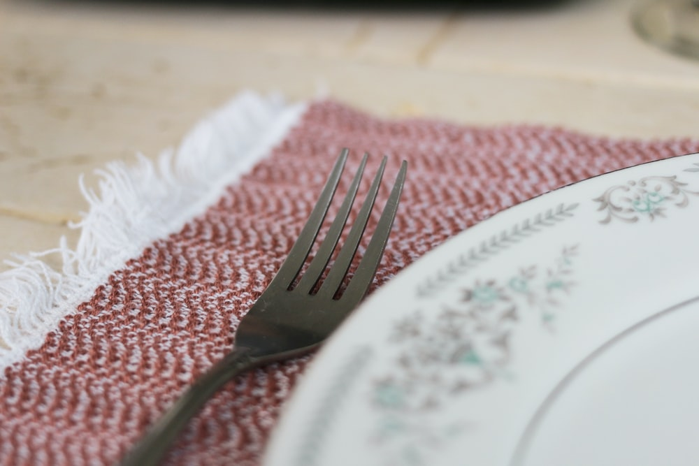 stainless steel fork on white and blue floral ceramic plate