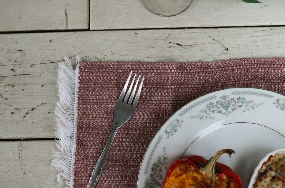 stainless steel fork on white and blue floral round plate
