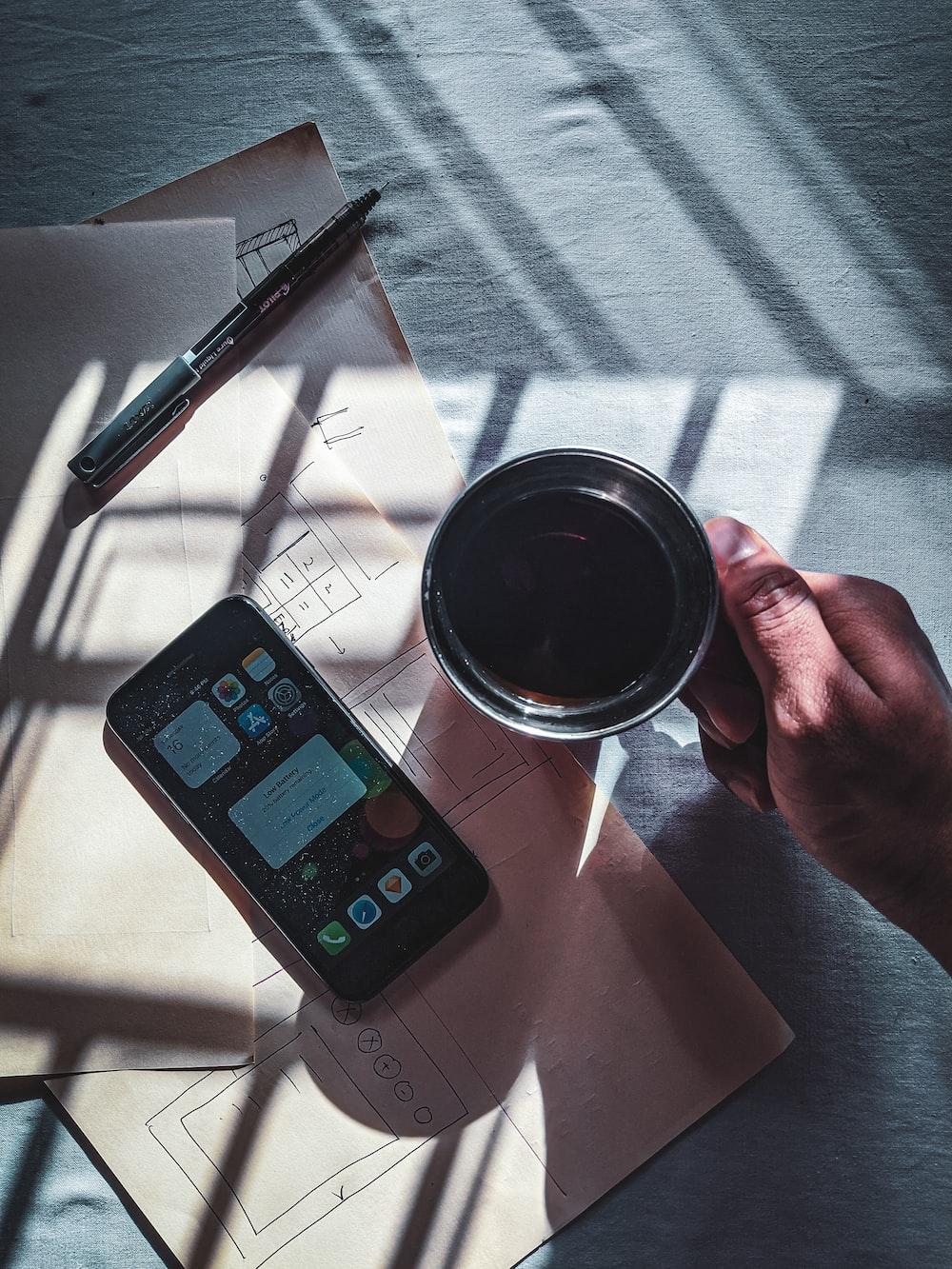 black iphone 4 beside black pen