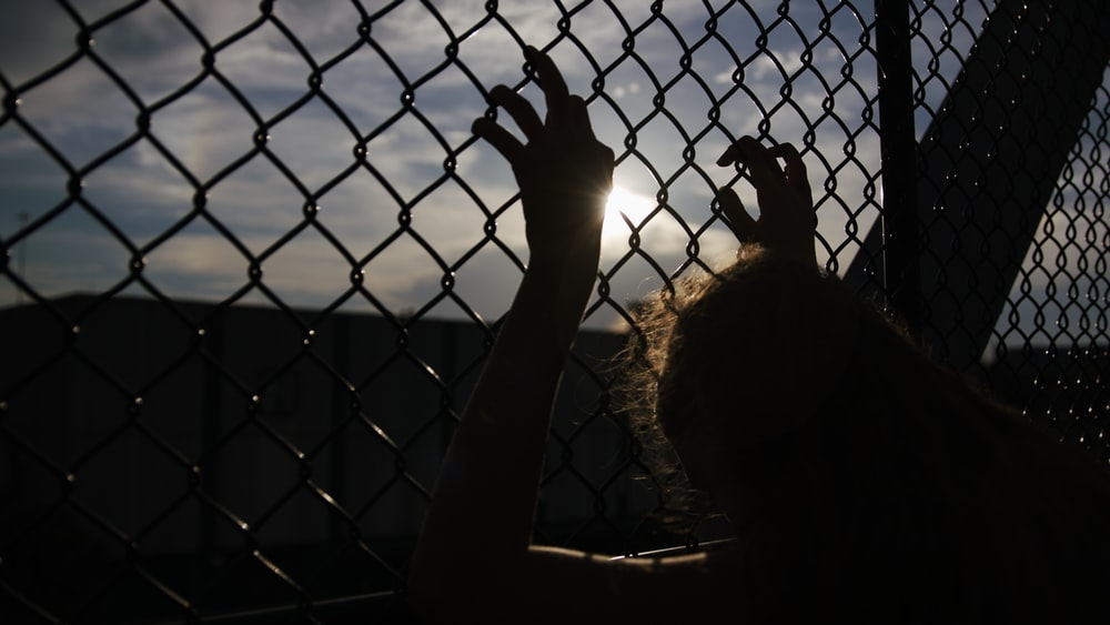 person holding on chain link fence