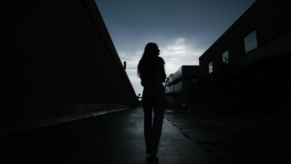 silhouette of woman walking on sidewalk during night time