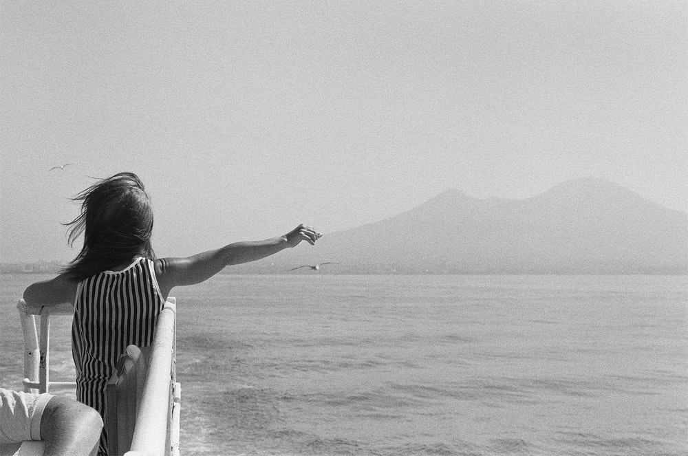 woman in black and white stripe dress standing on white boat during daytime
