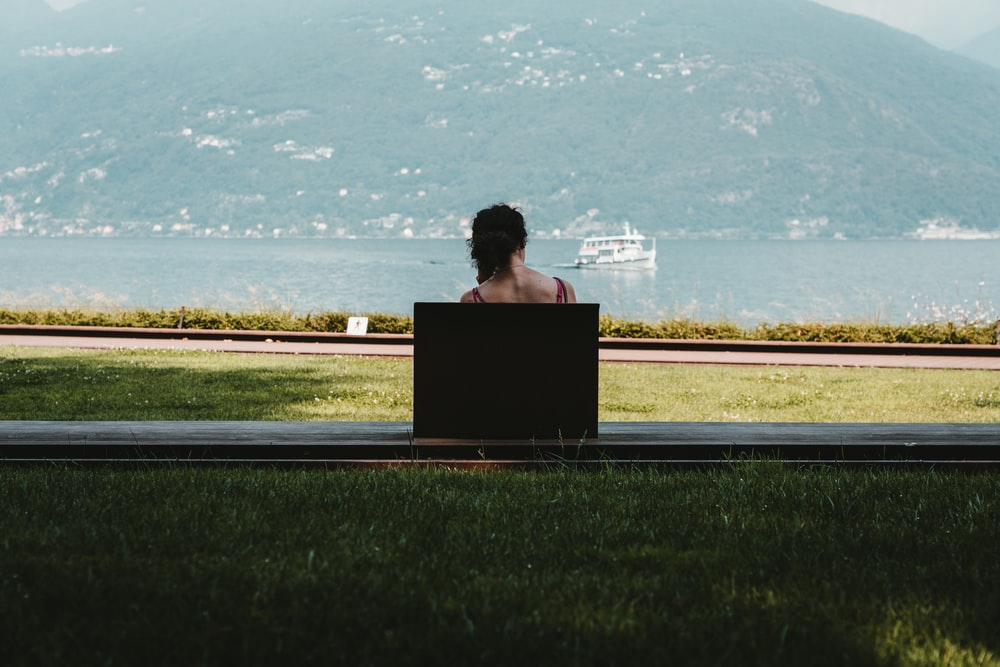 woman sitting on bench looking at the sea during daytime