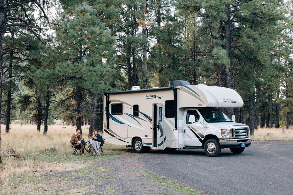people standing near white rv trailer during daytime