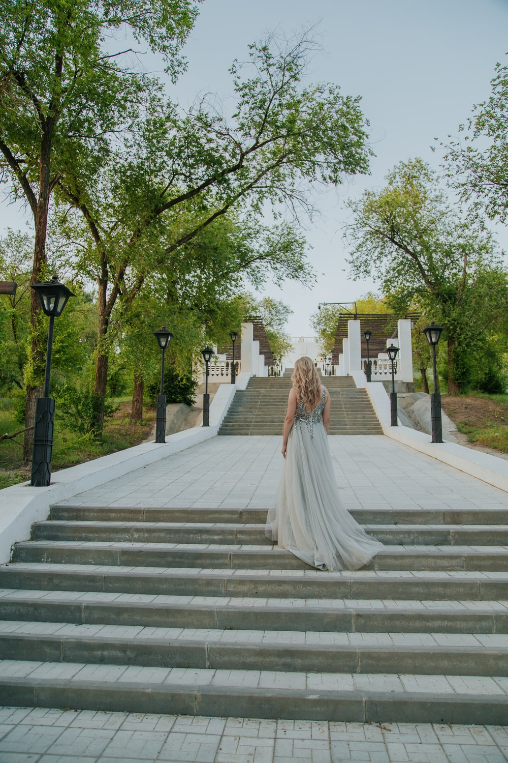 woman in white dress walking on gray concrete stairs