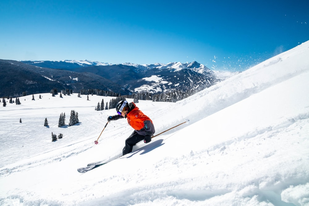 person in orange jacket and black pants riding ski blades on snow covered mountain during daytime