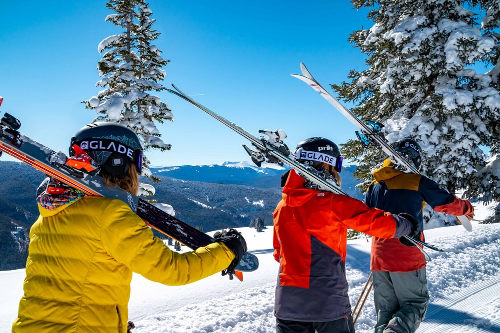 man in red jacket and black pants wearing white helmet riding on ski blades on snow