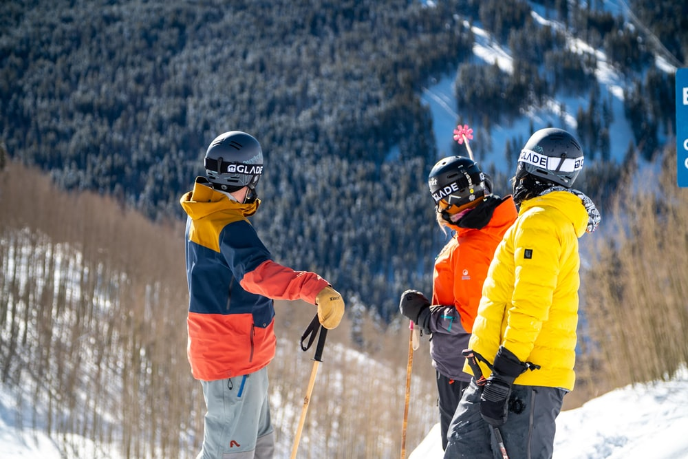 2 men in red and yellow jacket and helmet riding ski blades on snow covered mountain