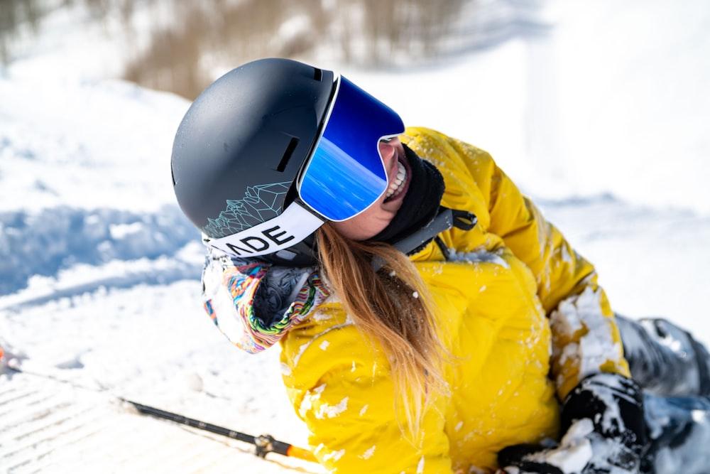 woman in yellow jacket wearing black helmet and black helmet