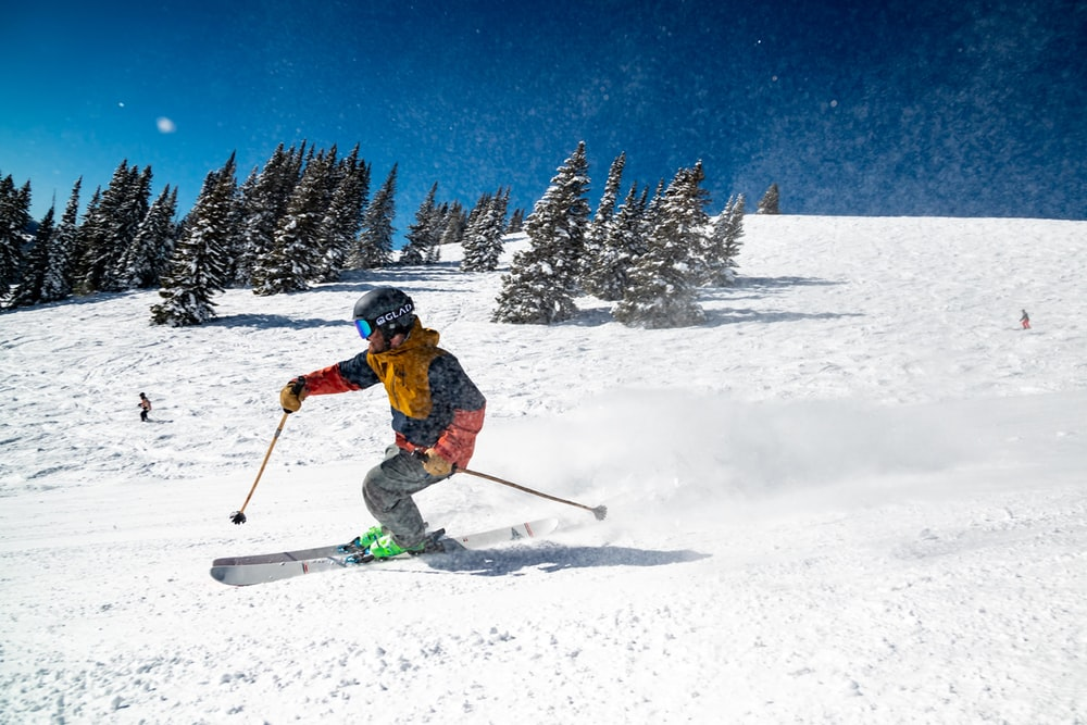 person in red jacket and blue pants riding on ski blades on snow covered ground during