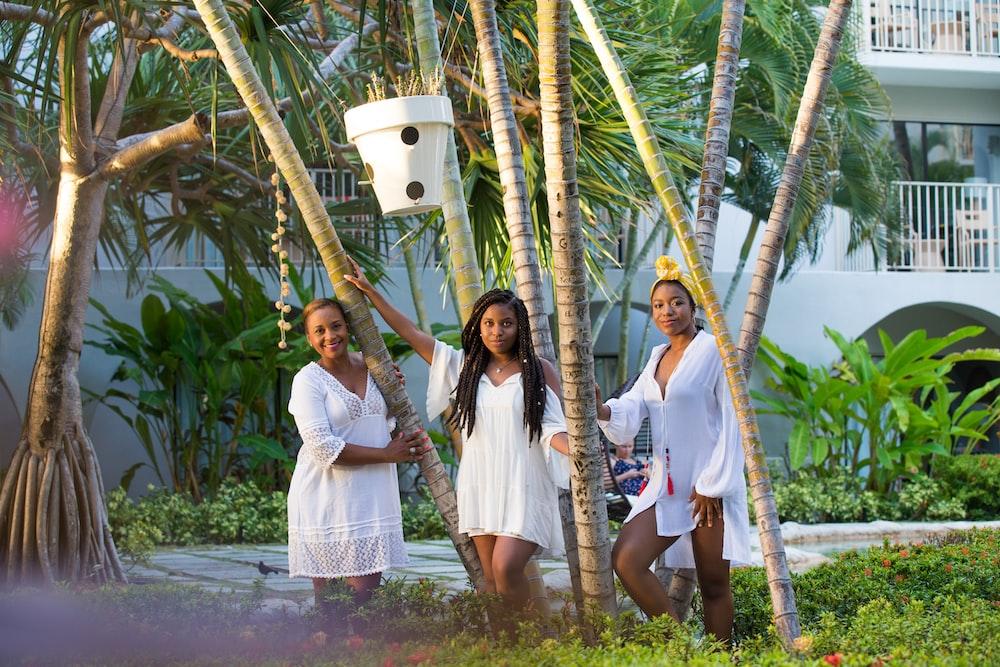 2 women standing near palm tree during daytime