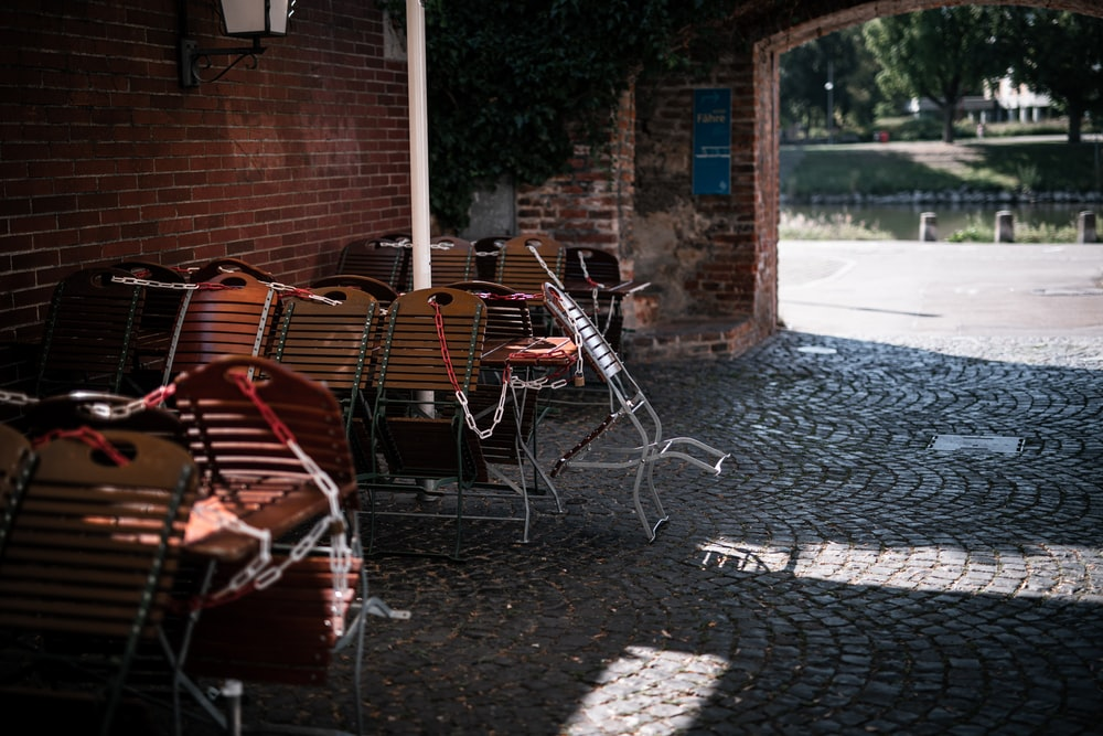 brown wooden chairs and tables near brown brick wall
