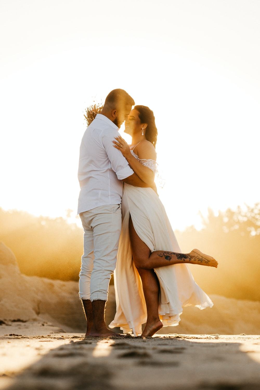 man and woman kissing during sunset