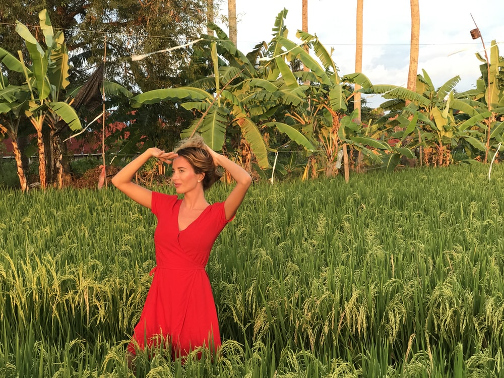 woman in red dress standing on green grass field during daytime