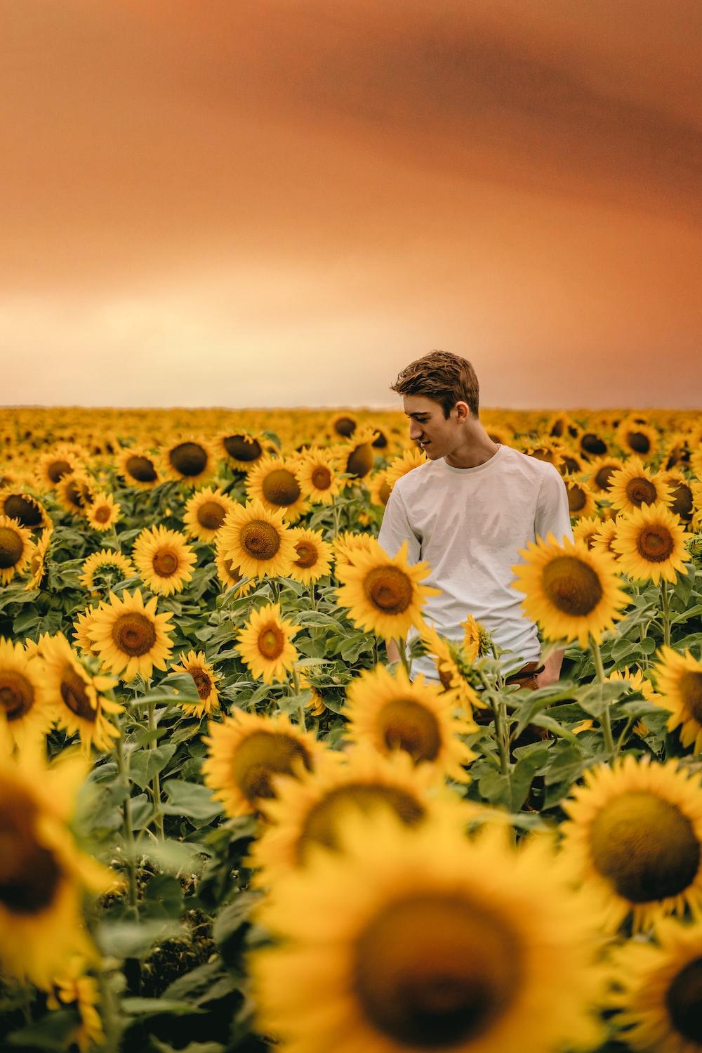 man in white dress shirt standing on sunflower field during daytime