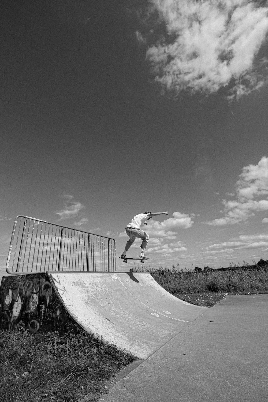 grayscale photo of man riding skateboard
