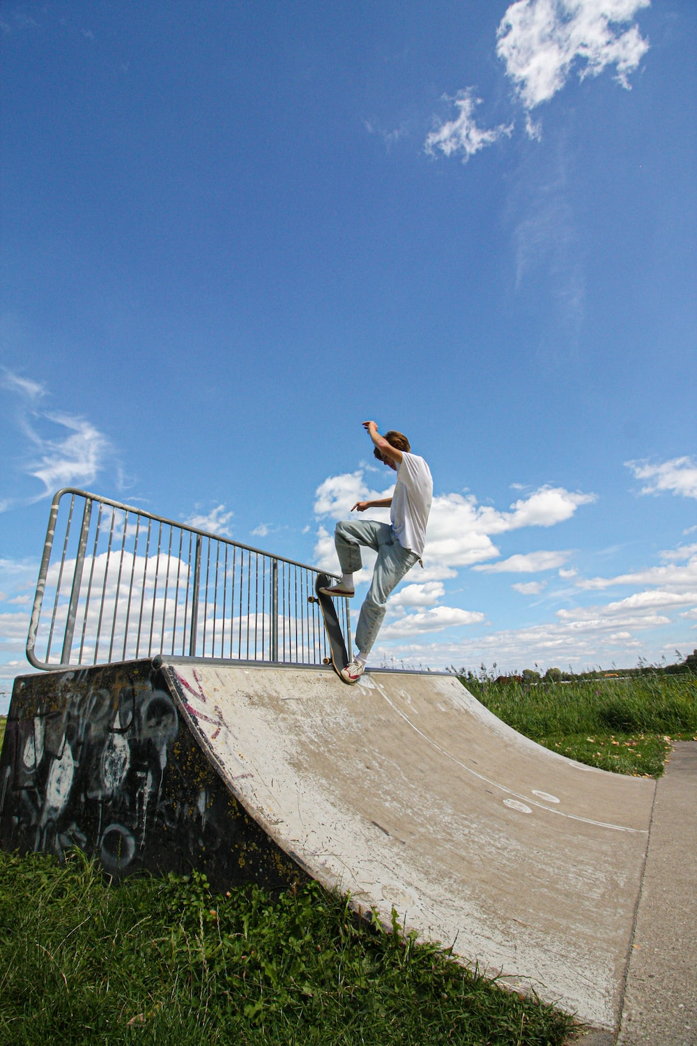 man in white long sleeve shirt and white pants jumping on brown concrete bridge during daytime