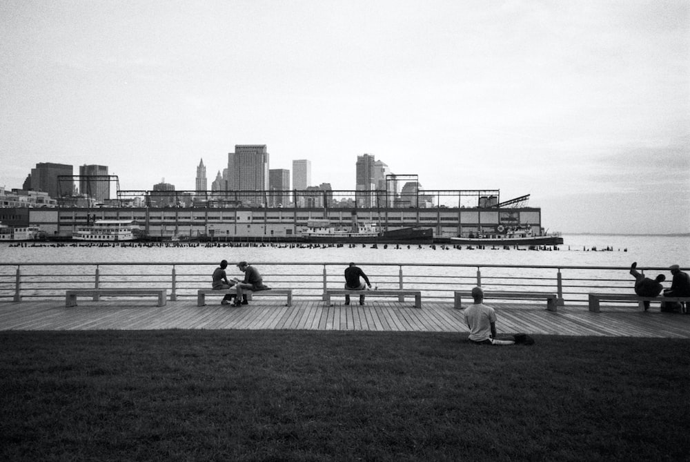 grayscale photo of people sitting on grass field near body of water