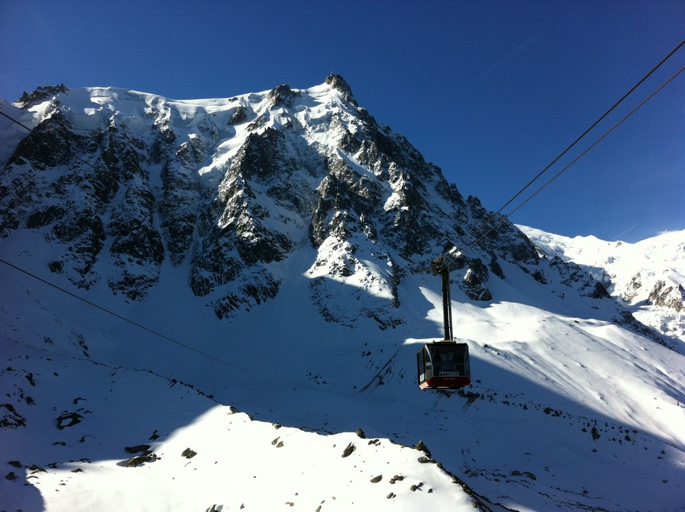 black cable car over snow covered mountain