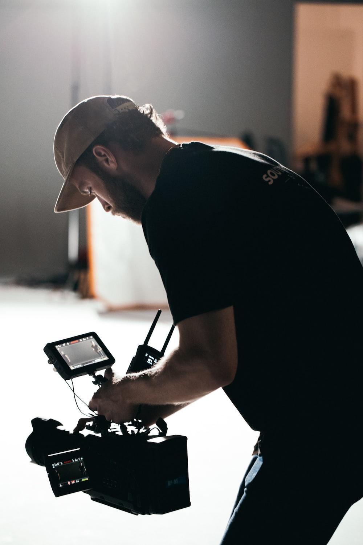 man in black t-shirt holding black digital camera