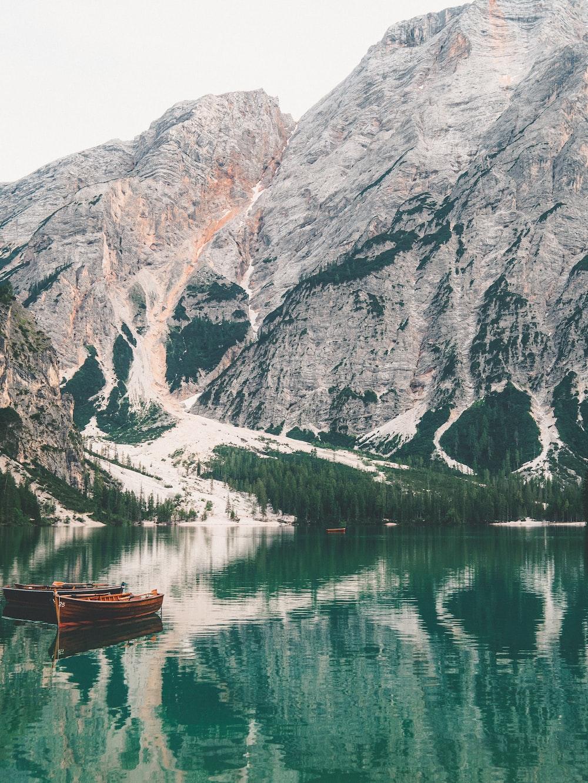 brown boat on lake near mountain during daytime