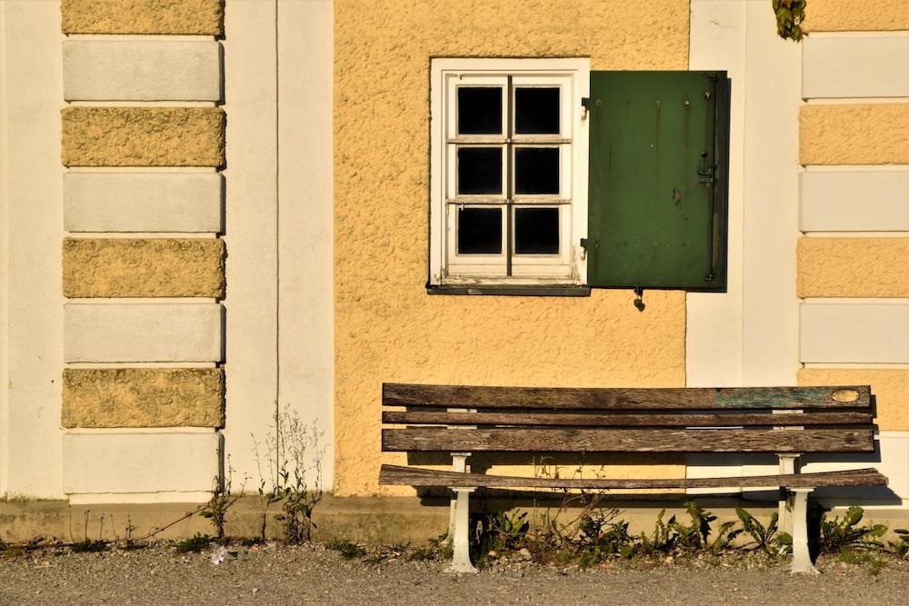 brown wooden bench beside window
