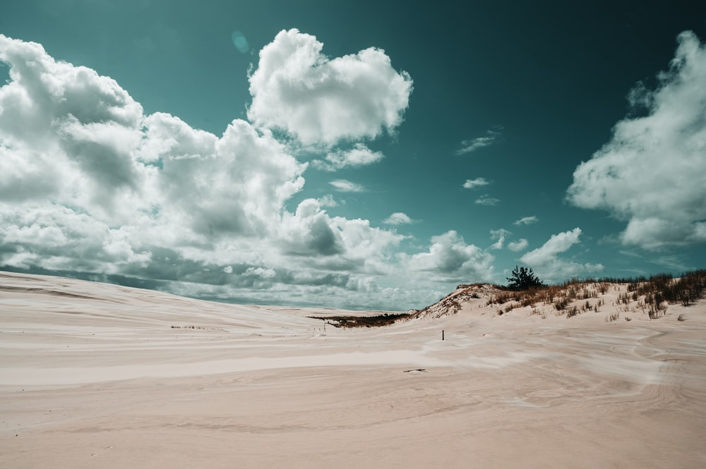 white sand under blue sky and white clouds during daytime