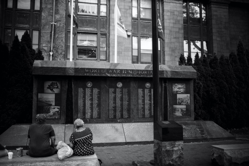 grayscale photo of man and woman sitting on bench near building