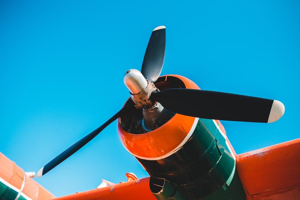 orange and black plane under blue sky during daytime