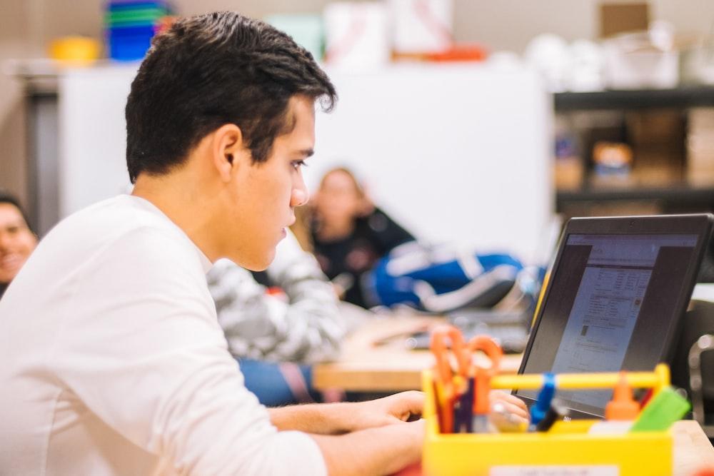 man in white long sleeve shirt using black laptop computer