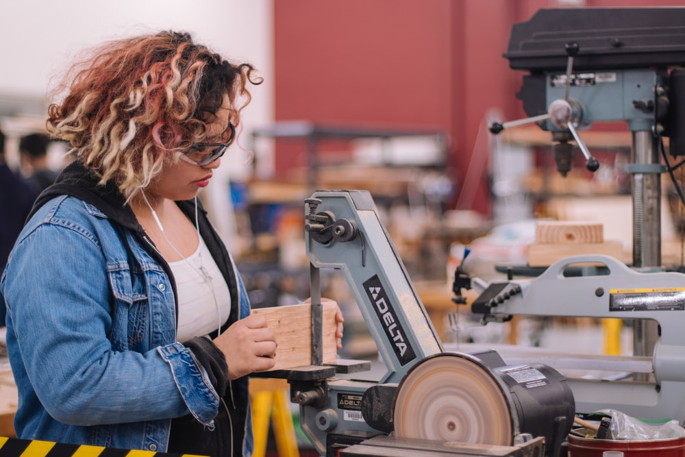 woman in blue denim jacket holding white and black power tool