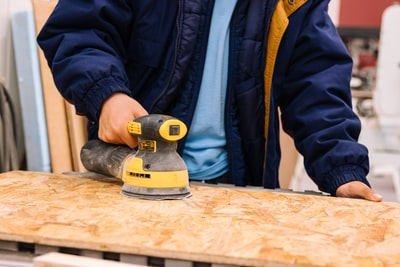 person holding black and yellow cordless hand drill