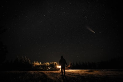 man and woman walking on dirt road during night time asteroid teams background
