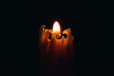 A candle burning in the dark.