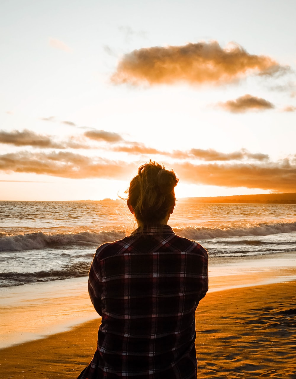 woman in black and white plaid dress shirt standing on seashore during sunset