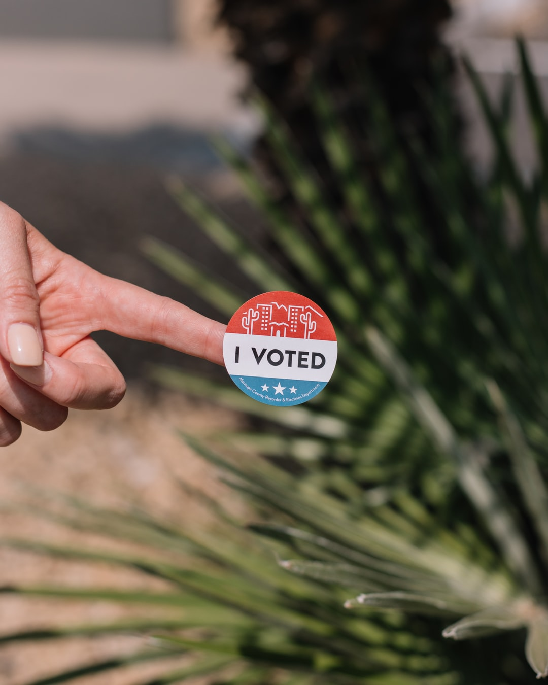 Arizona desert themed I voted voting sticker with palm tree and desert landscaping in background.